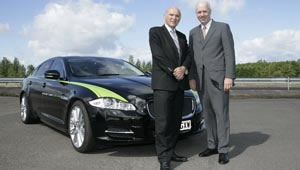 Vince Cable and Carl-Peter Forster, Managing Director and Group CEO of Tata Motors, shake hands in front of a Jaguar Limo Green during their visit to Jaguar Land Rover's Advanced Research team